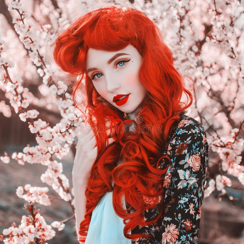 Young beautiful redhead girl on spring flower background. Woman with pale skin and long red hair in flower dress. Blooming spring royalty free stock image