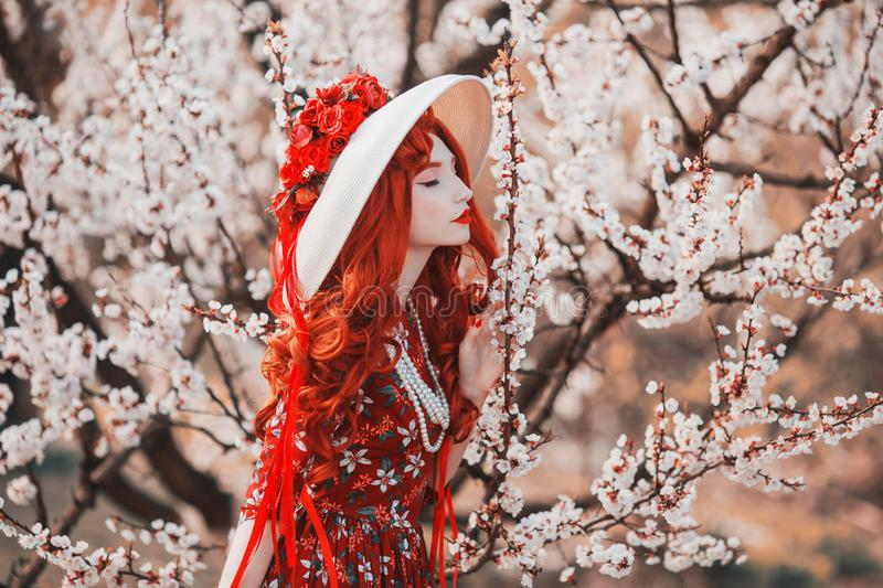 Young beautiful redhead girl on spring flower garden. Woman with long red hair in dress sniff flower on nature. Sweet aroma. stock photo