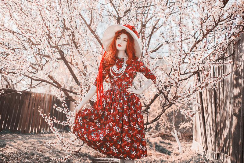 Young beautiful redhead girl with on spring flower garden. Woman with long red hair in retro dress on nature. Blooming spring stock photography