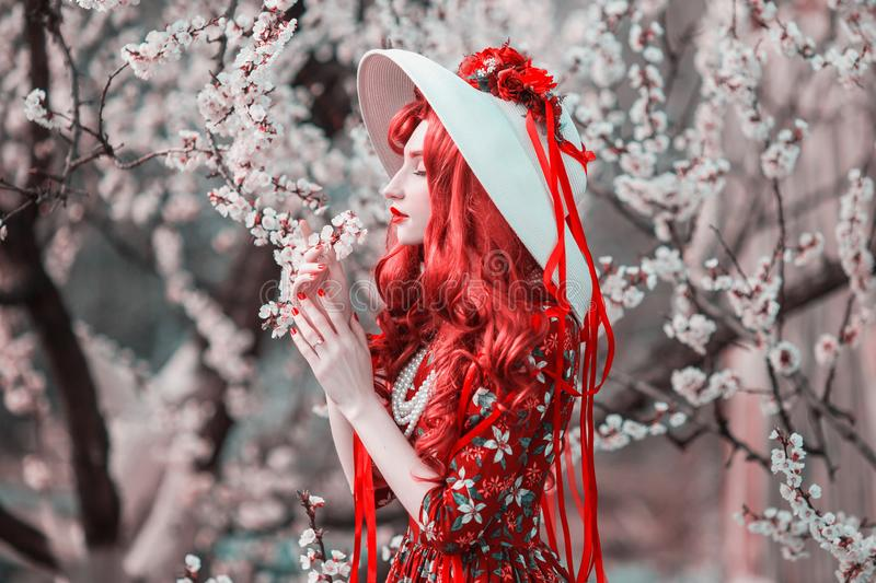 Young beautiful redhead girl in spring flower garden. Woman with long red hair in retro dress on nature. Flower smell. Blooming. Spring cherry tree. Stylish royalty free stock image