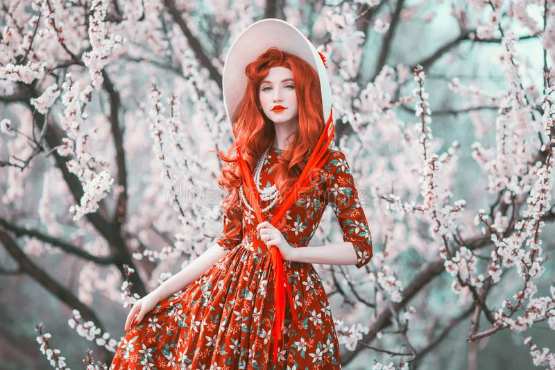 Young beautiful redhead girl in spring flower garden. Woman with long red hair in retro dress on nature. Flower smell. Beautiful. Spring cherry tree. Stylish royalty free stock images