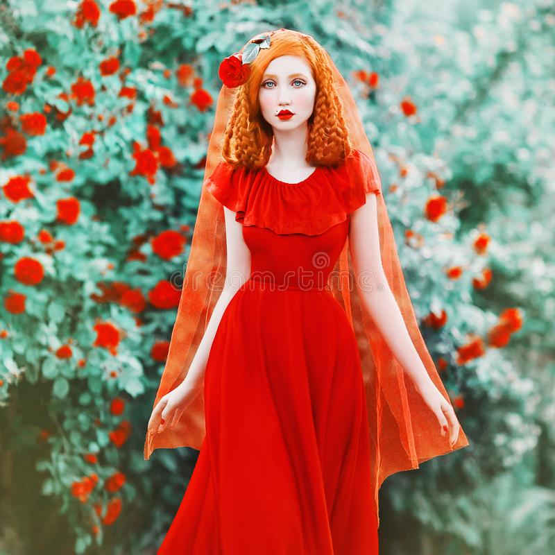 Young beautiful redhead girl with very long hair braided in plait. Fabulous renaissance woman in a red dress against the backdrop. Of a beautiful rose bush royalty free stock image
