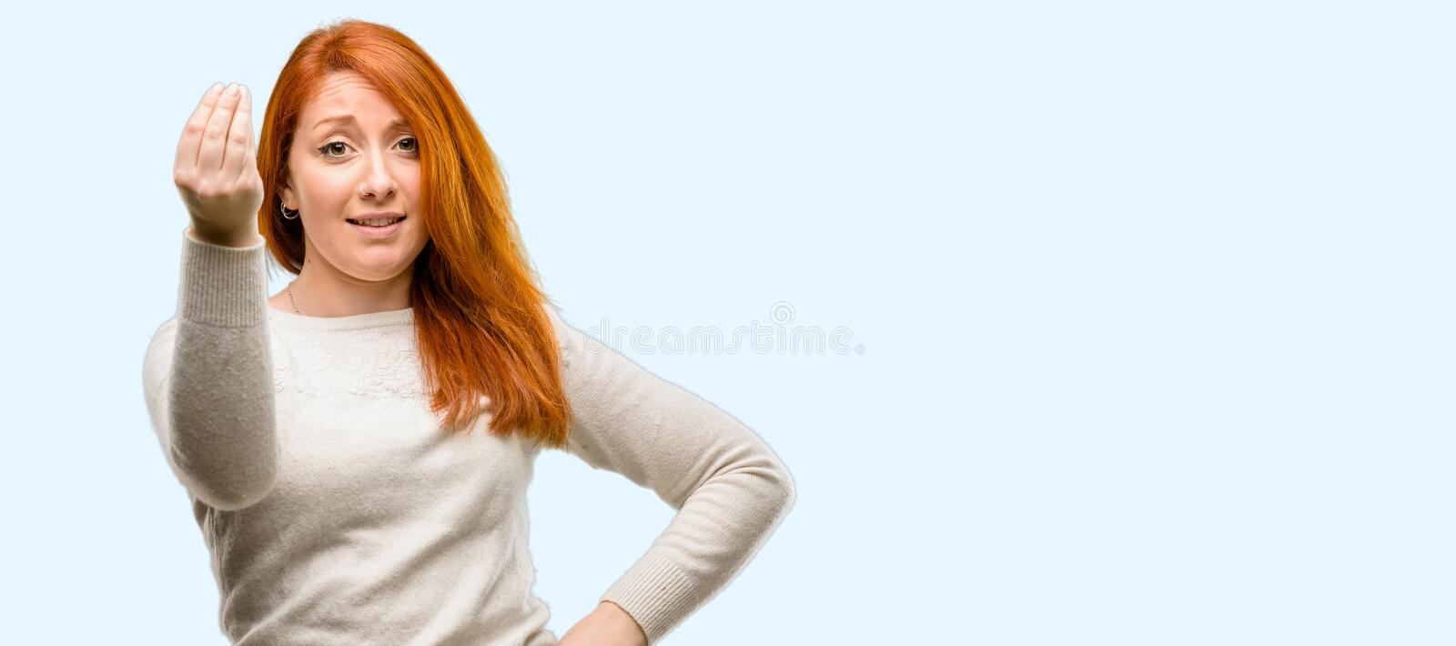 Young beautiful redhead woman over blue background stock image