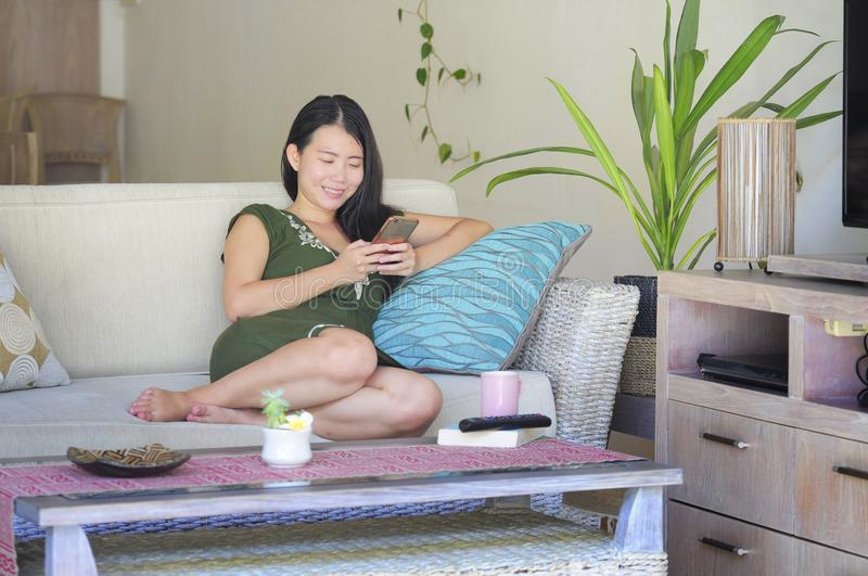 Young beautiful and relaxed Asian Chinese woman lying at home living room sofa couch using internet on mobile phone happy and comf. Ortable at modern sweet villa stock images