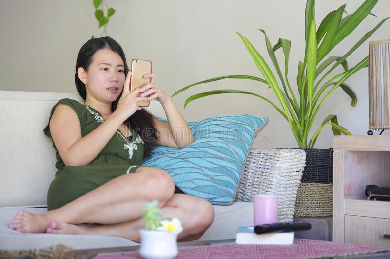 Young beautiful and relaxed Asian Chinese woman lying at home living room sofa couch using internet on mobile phone happy and comf. Ortable at modern sweet villa stock photos