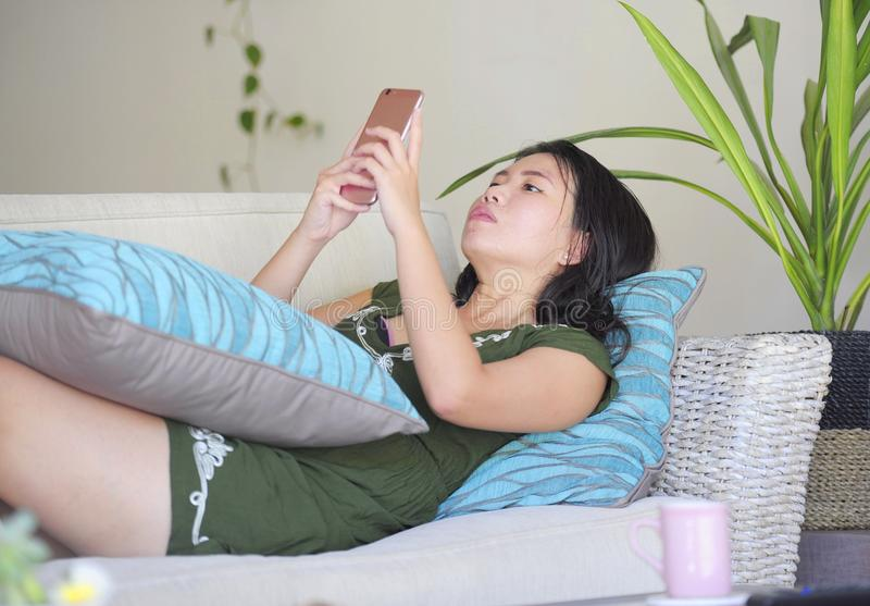 Young beautiful and relaxed Asian Chinese woman lying at home living room sofa couch using internet on mobile phone happy and comf. Ortable at modern sweet villa stock photo