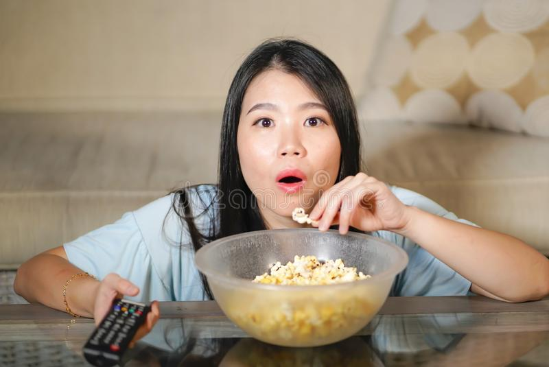 Young beautiful and relaxed Asian Japanese woman watching Korean drama on television on sad romantic movie eating popcorn at home. Living room couch stock photo