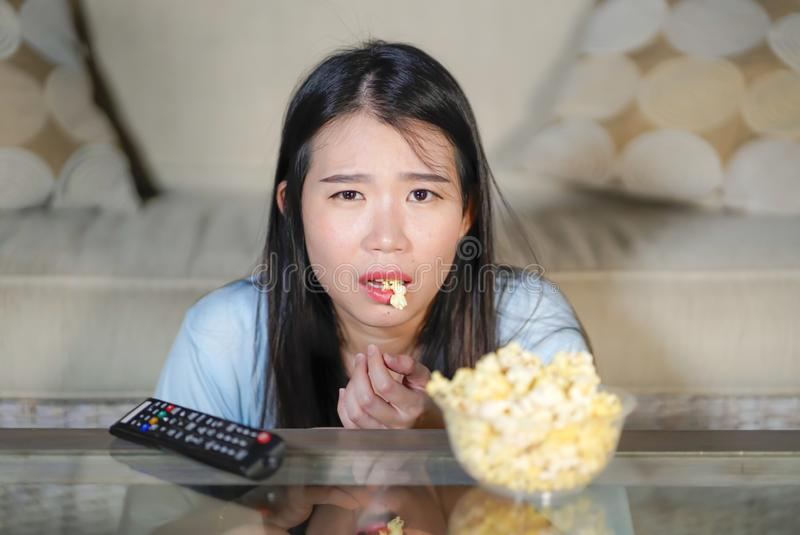 Young beautiful and relaxed Asian Japanese woman watching Korean drama on television on sad romantic movie eating popcorn at home. Living room couch stock image
