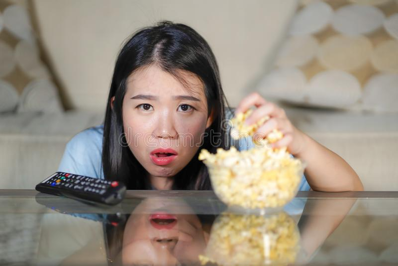 Young beautiful and relaxed Asian Japanese woman watching Korean drama on television on sad romantic movie eating popcorn at home. Living room couch stock photos