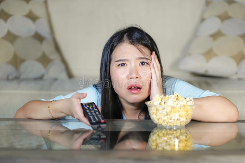 Young beautiful and relaxed Asian Japanese woman watching Korean drama on television on sad romantic movie eating popcorn at home. Living room couch royalty free stock photos
