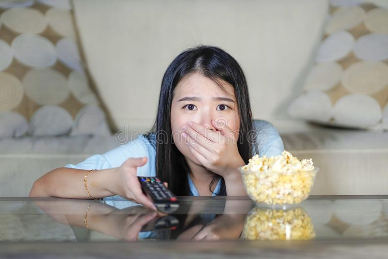 Young beautiful and relaxed Asian Japanese woman watching Korean drama on television on sad romantic movie eating popcorn at home. Living room couch stock photography
