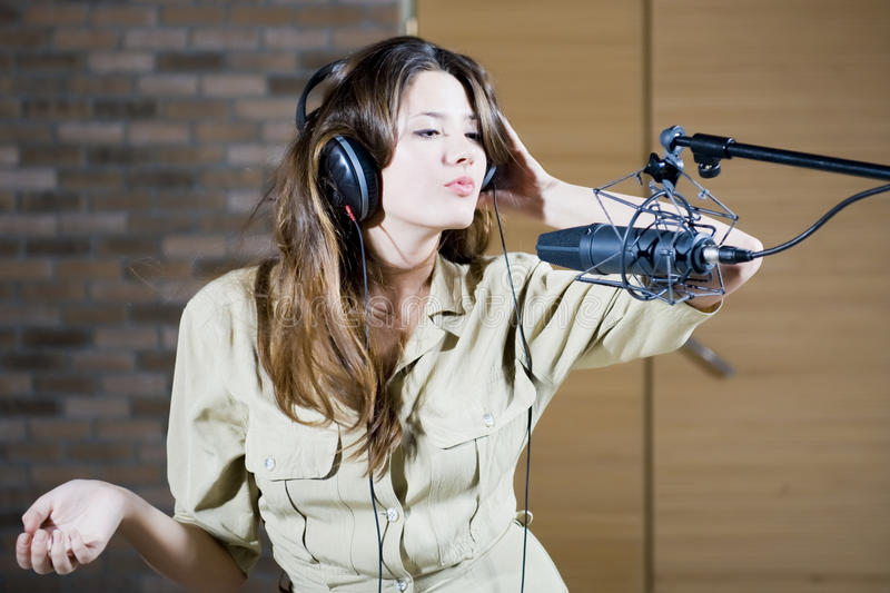 Young beautiful retro woman recording the sound