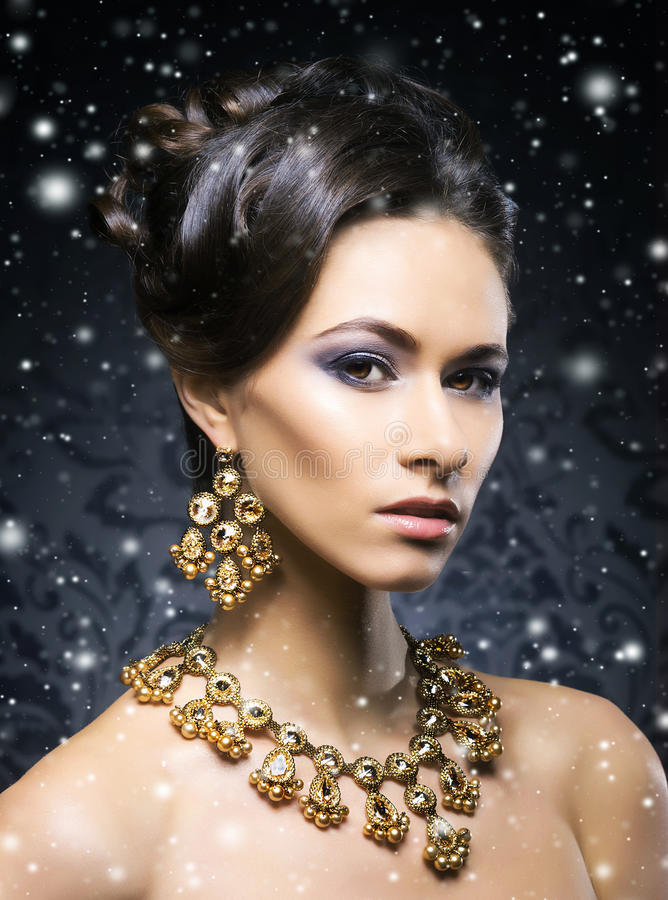 Young, beautiful and rich woman in jewels. Of platinum and stones over winter Christmas background stock images