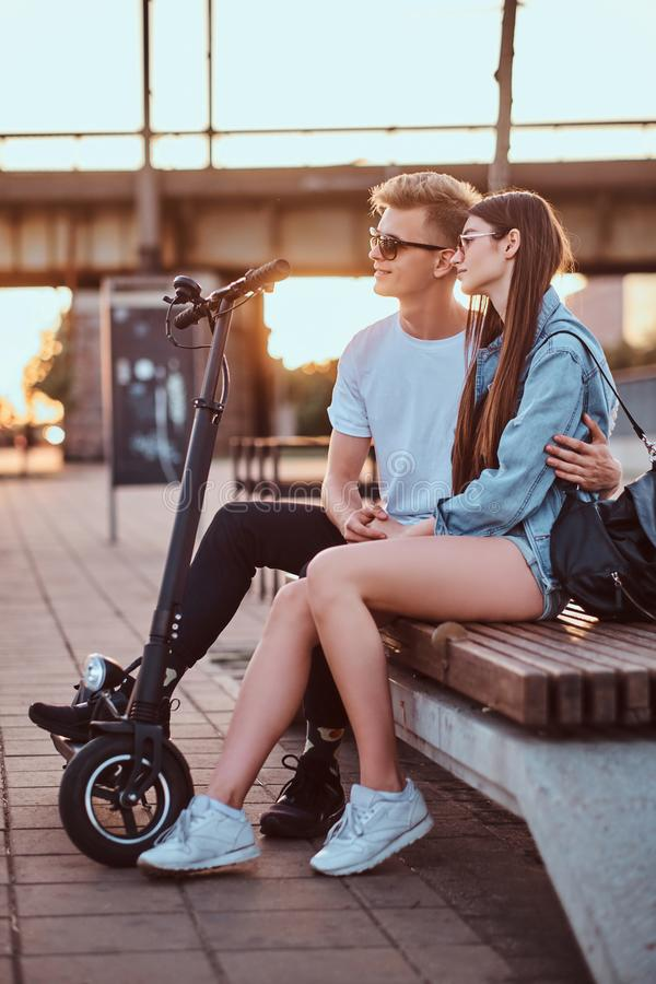 Attractive couple enjoying sunset with their scooters. Young beautiful romantic couple with electric scooters is sitting on the bench near brige at sunset time stock photos