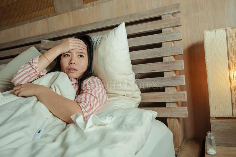 Young beautiful sad and depressed Asian Chinese woman lying in bed suffering cold and flu at night feeling unwell at nigh in. Young beautiful sad and depressed stock photography