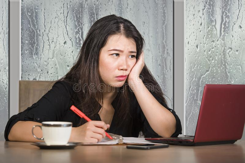Young beautiful sad and depressed Asian Korean businesswoman working exhausted and frustrated at office computer desk with rain on royalty free stock image