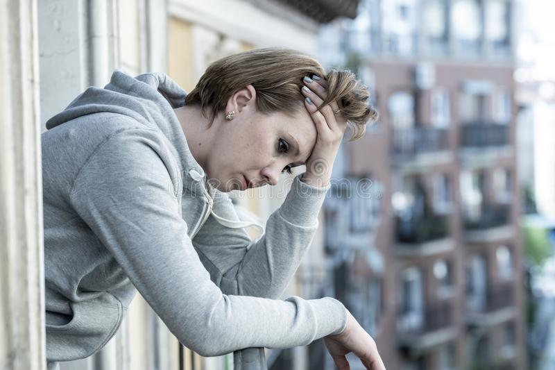 Young beautiful sad woman suffering depression looking worried on home balcony with an urban view stock images