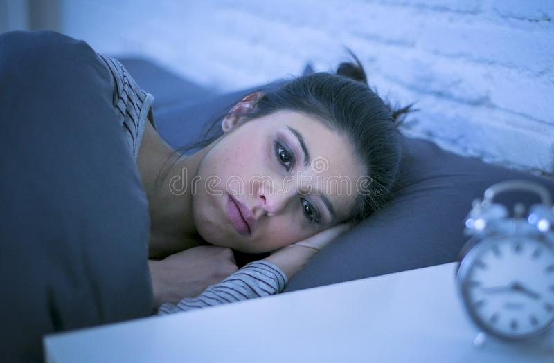 Young beautiful sad and worried latin woman suffering insomnia and sleeping disorder problem unable to sleep late at night lying o stock image