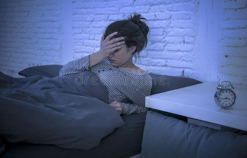 Young beautiful sad and worried latin woman suffering insomnia and sleeping disorder problem unable to sleep late at night lying o royalty free stock photo