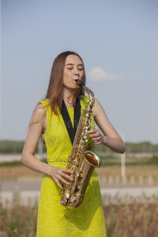 Young beautiful saxophonist with saxophone - outdoor in nature royalty free stock photo