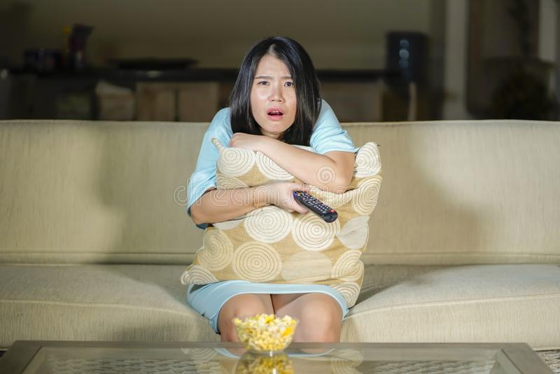 Young beautiful and scared Asian Chinese teenager woman in fear watching horror scary movie at home sofa couch eating popcorn bowl royalty free stock photos