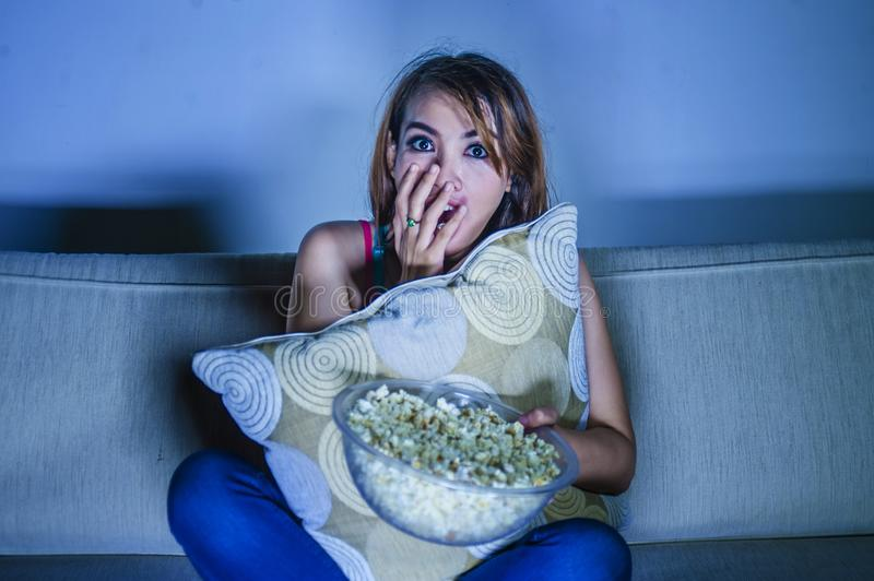 Young beautiful and scared woman watching horror or suspense movie eating popcorn sitting at home sofa couch late night in panic. Young beautiful and scared royalty free stock images