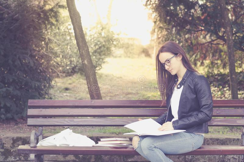 Young beautiful school or college girl with eyeglasses sitting on the bench in the park reading the books and study for exam, educ royalty free stock photography