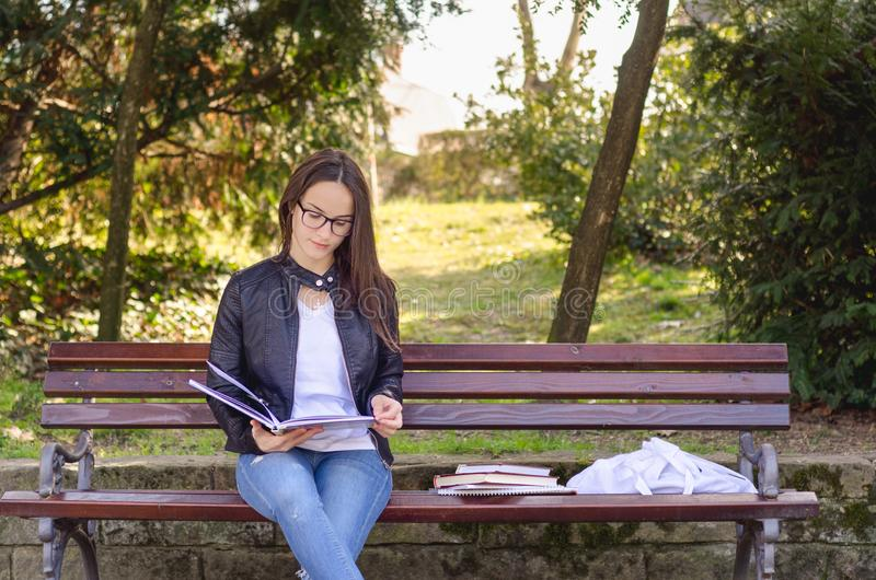 Young beautiful school or college girl with eyeglasses sitting on the bench in the park reading the books and study for exam stock images