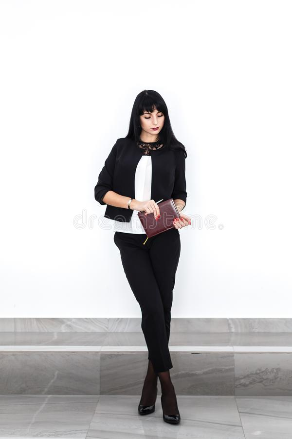 Young beautiful serious brunette woman with a note book dressed in a black business suit  standing against the white wall in stock photography