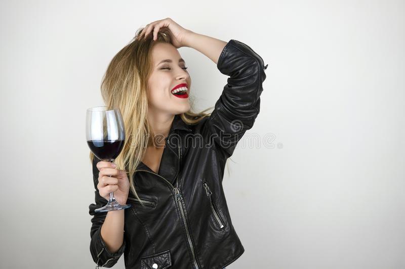 Young beautiful sexy blonde woman wearing black leather jacket drinks wine from glass laughing on isolated white stock photo