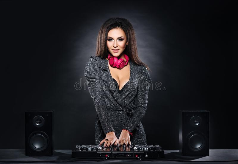 Young, beautiful and dj girl playing music on a disco party in a night club stock photo