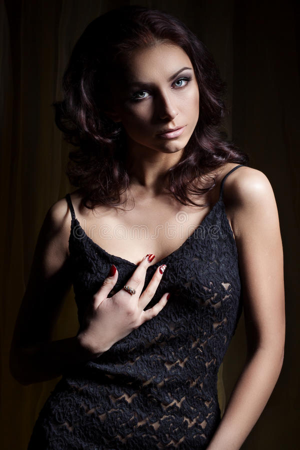 Young beautiful girl with a gentle makeup and beautiful hair in a black lace dress with dark lighting in the Studio stock images
