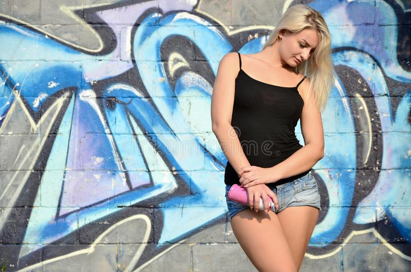 A young and beautiful girl graffiti artist with a paint spray stands on the wall background stock photography