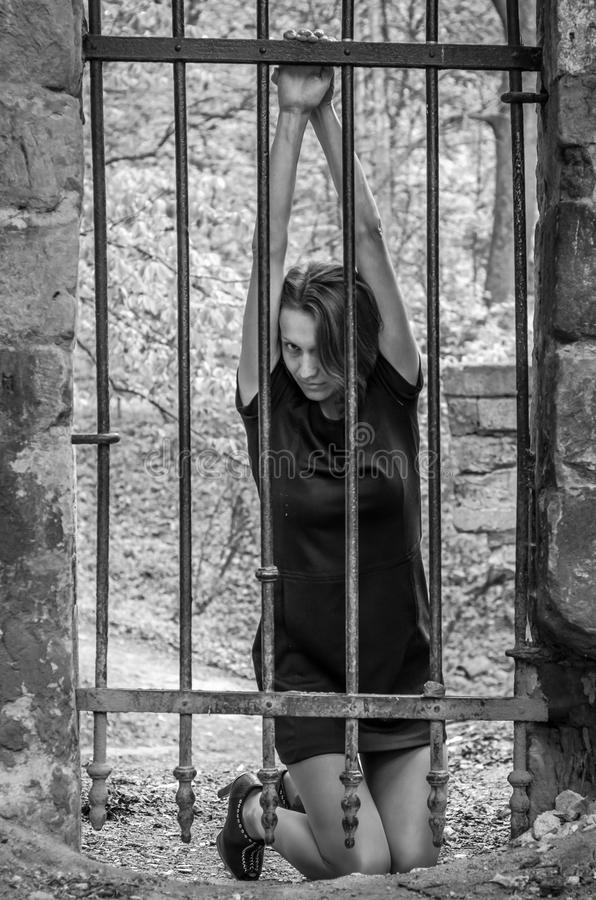 Young beautiful girl prisoner behind an iron fence royalty free stock photo
