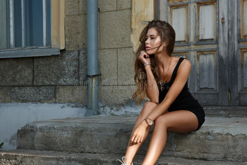 Young beautiful and girl with slim sun tanned attractive body dressed in a slinky black singlet is posing outdoor stock image