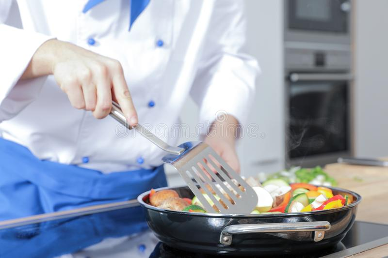 Beautiful woman man couple as a cook are cooking in a kitchen royalty free stock photography