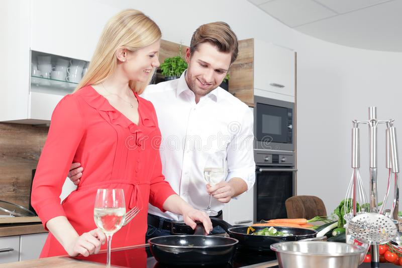 Beautiful woman man couple as a cook are cooking in a kitchen royalty free stock photo
