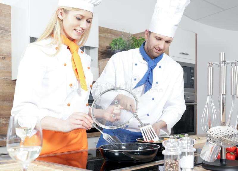 Beautiful woman man couple as a cook are cooking in a kitchen stock photography