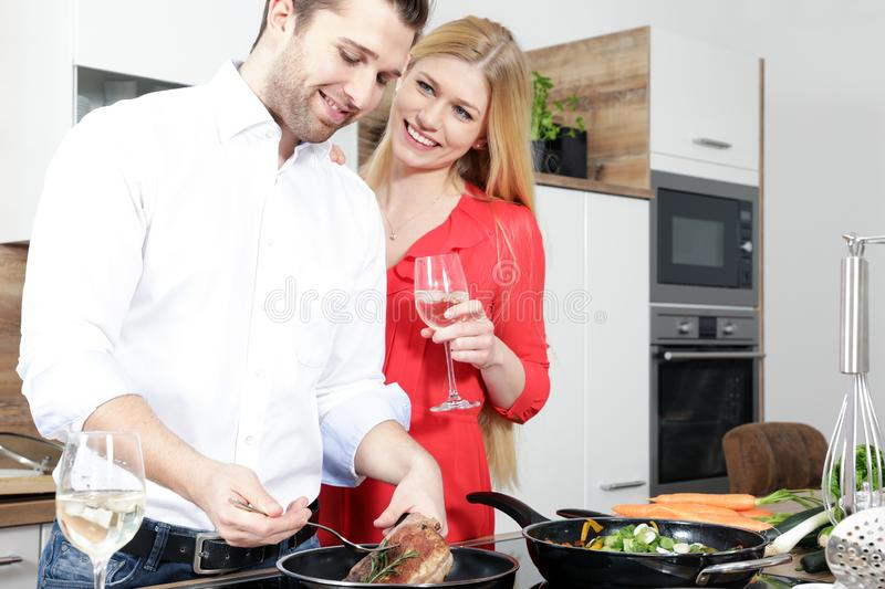 Beautiful woman in a red dress man couple as a cook are cooking in a kitchen stock images