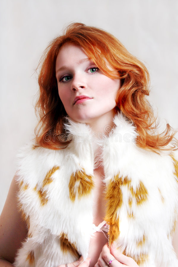 Young beautiful red woman in fur royalty free stock photography