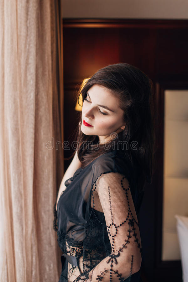 Young beautiful woman in a black lace dressing gown posing in a room royalty free stock image