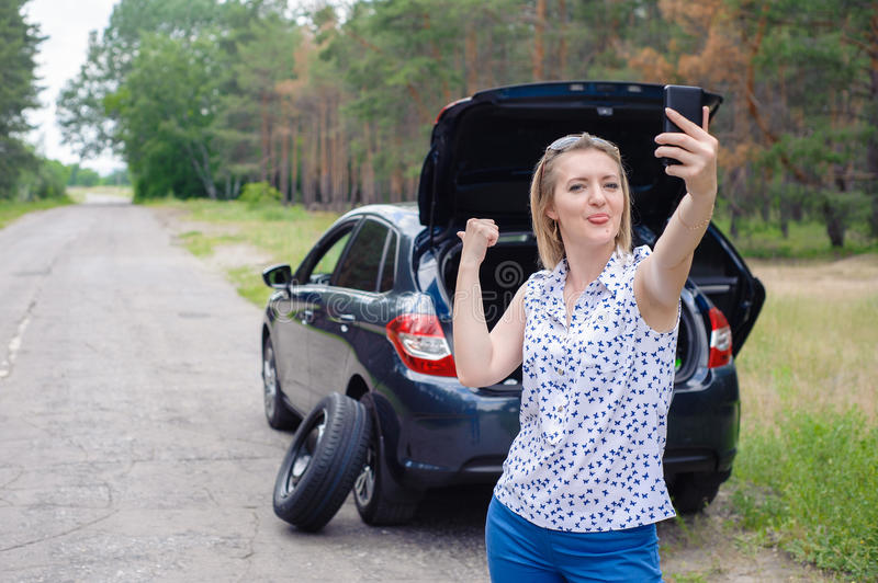 Young beautiful woman at broken car with mobile phone, stan. Ding in the public road in forest area, calling for help with mobile phone. Broken vehicle in the stock images