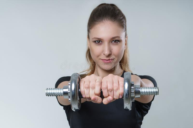 Young beautiful woman with brunette hair in a black t-shirt with metal dumbbells, portrait fitness sport photo. Young beautiful woman with brunette hair in a royalty free stock image