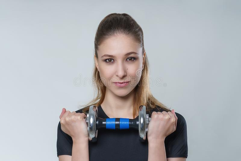 Young beautiful woman with brunette hair in a black t-shirt with metal dumbbells, portrait fitness sport photo. Young beautiful woman with brunette hair in a royalty free stock images