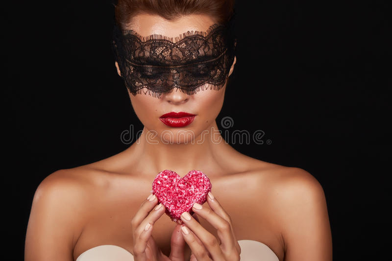 Young beautiful woman with dark lace on eyes bare shoulders and neck, holding cake shape of heart to enjoy the taste and are. Dieting, feeling temptation, teeth royalty free stock images