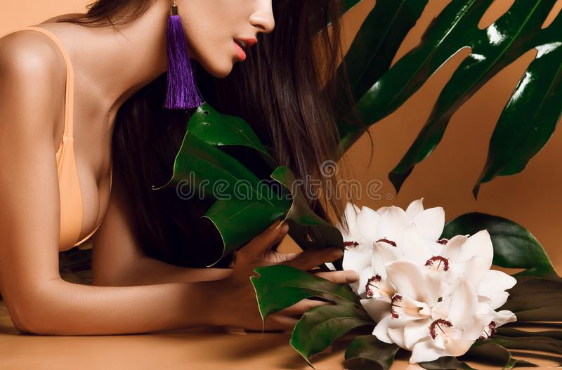 Young beautiful sexy woman with perfect smooth skin hold tropical leaves and orchid flowers stock image