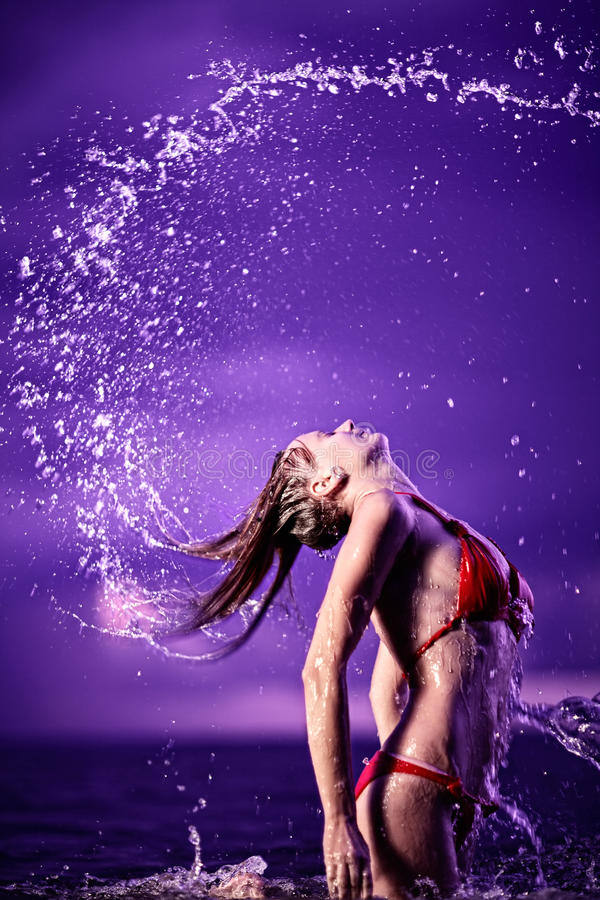 Young beautiful woman in red bikini jumping out of the water with splash. royalty free stock images