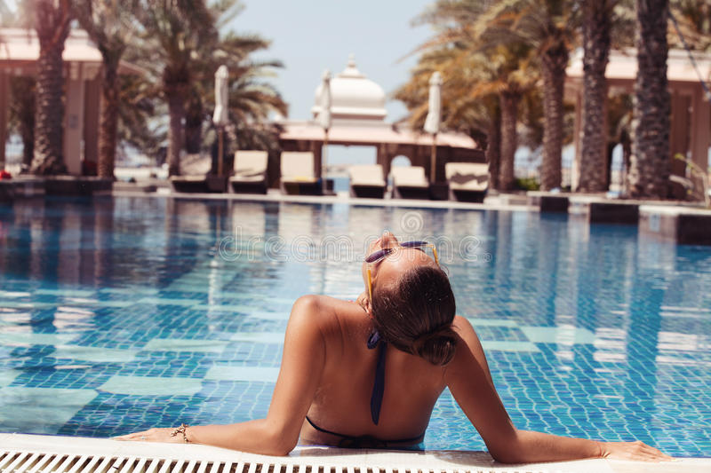 Young beautiful woman standing in blue water of swimming po. Woman relaxing in in the water in luxury swimming pool. Summer vacation royalty free stock photos
