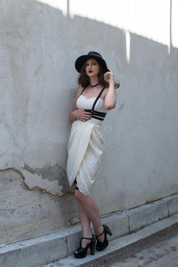 Young beautiful woman wearing trendy outfit, white dress, black hat and leather swordbelt. Longhaired brunette royalty free stock photo