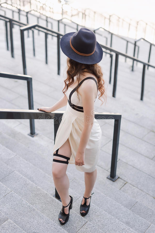 Young beautiful woman wearing trendy outfit, white dress, black hat and leather swordbelt. Longhaired brunette stock photo
